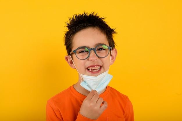 Ребенок рад снять маску для лица от коронавируса covid-19 на желтом