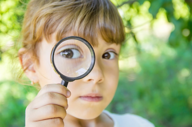 The child is looking in a magnifying glass. increase.