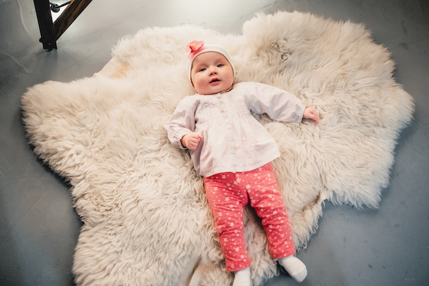 The child is lying on a woolen carpet and smiles at the camera