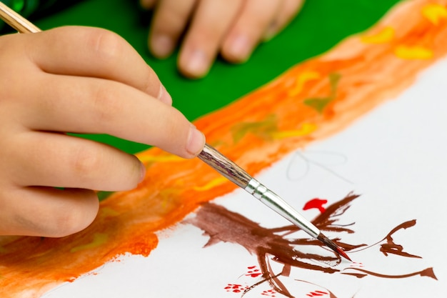 The child is painting a autumn tree with a brush