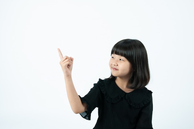 The child is pointing his finger at the white background.
