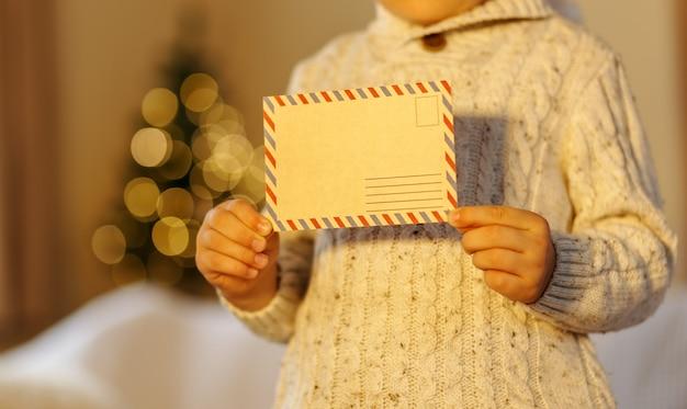 子供がサンタクロースに手紙を投稿している人気の子供たちクリスマスの活動新年のツリーがぼやけている