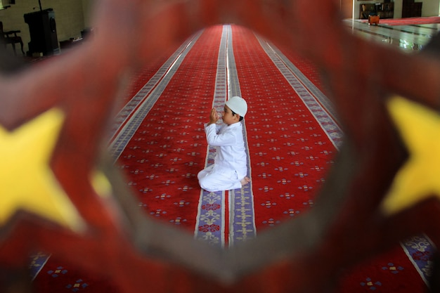 A child is praying at the mosque
