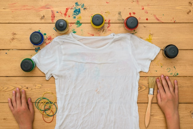 The child is preparing to apply paint on a t-shirt in the style of tie dye