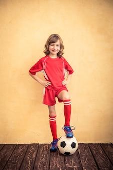 아이가 축구 선수 인 척하고 있습니다. 성공과 승자 개념