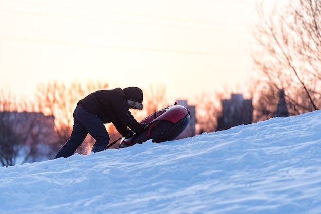 A child is pulling tubing on a snowy mountain at sunset