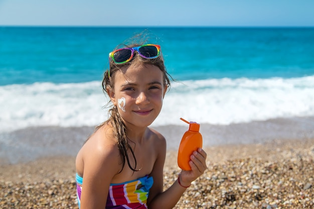 The child is putting sunscreen on her face. selective focus. kid.