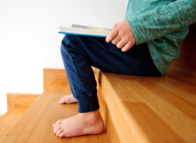 The child is reading the paper book sitting on the wooden stairs in the house