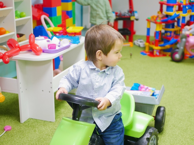 The child is riding a toy car. a child plays with toys at home. little child plays with toys in kindergarten. boy in toy car