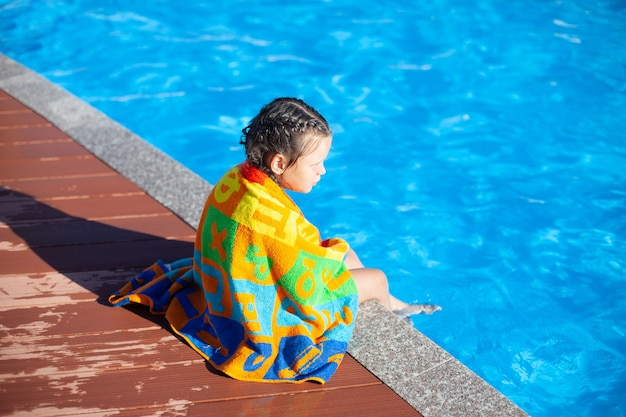 Child is sitting by pool little girl with braided pigtails is sitting on side of pool and wrapped in...