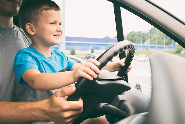 The child is sitting on the father's knees in the car and learning how to drive the car