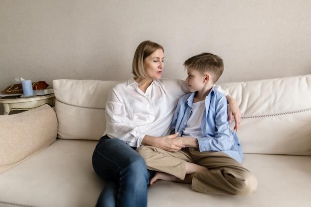 Ребенок сидит с взрослой женщиной, обнимающейся и болтающей.