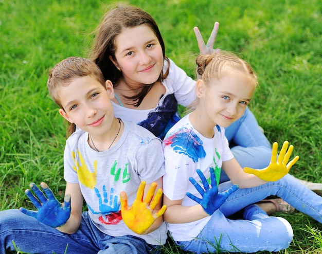 The child is smeared with brightly colored finger paints clothes smiling in the park.