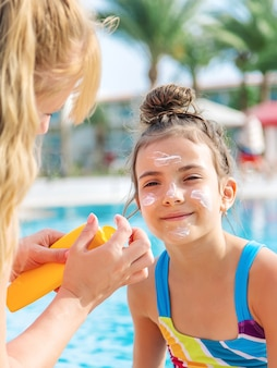 The child is smearing sunscreen on the mother