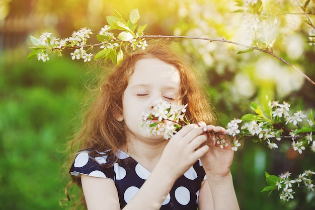 The child is smelling blooming cherry branch