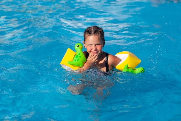 子供はプールで泳いでいます恐竜がプールでポーズをとって浮き輪で幸せな少女は泳ぐことを学びます
