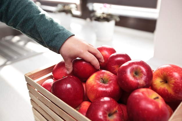 The child is taking the juicy red apple from the basket