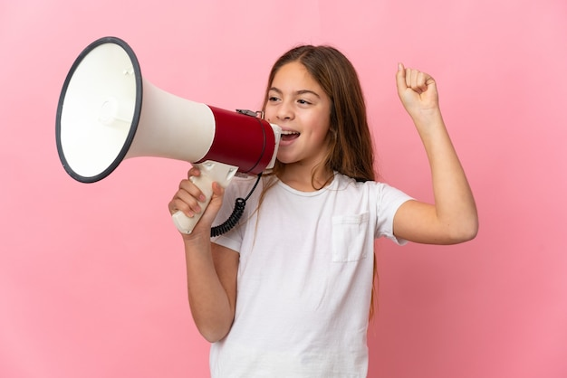 Child over isolated pink background shouting through a megaphone to announce something in lateral position