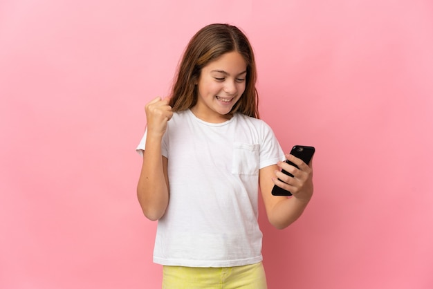 Child over isolated pink background using mobile phone and doing victory gesture