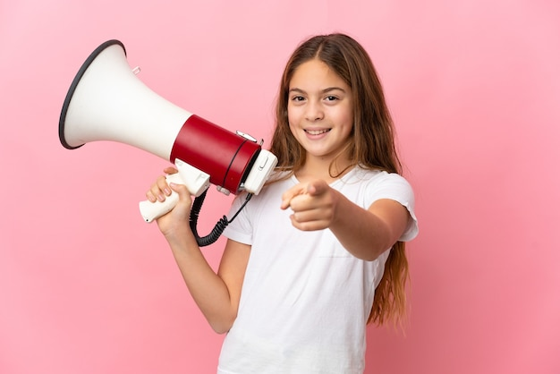 Child over isolated pink wall holding a megaphone and smiling while pointing to the front