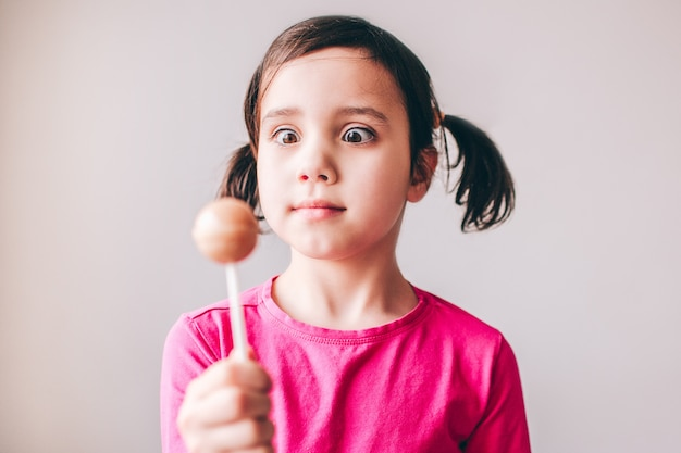 Child isolated over wall. hold colorful lollipop in hand and look at it. tasty sugary lollipop. serious concentrated girl.