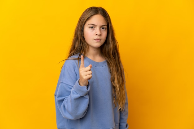 Child over isolated yellow background frustrated and pointing to the front