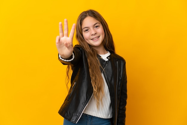 Child over isolated yellow background happy and counting three with fingers