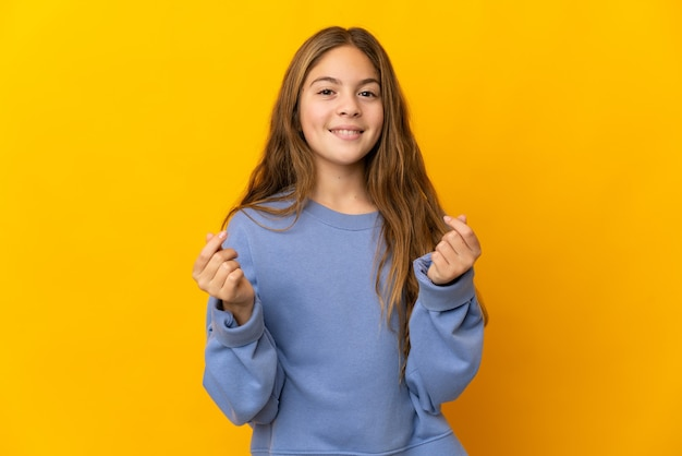 Child over isolated yellow background making money gesture