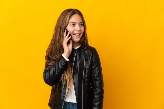 Child over isolated yellow wall keeping a conversation with the mobile phone