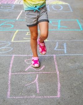 舗装で古典をジャンプする子供。セレクティブfocus.child