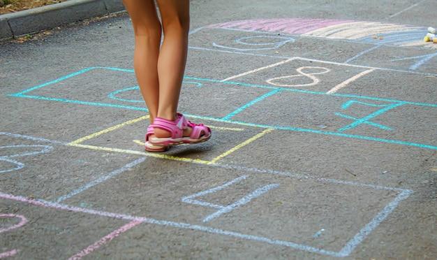 舗装で古典をジャンプする子供。セレクティブフォーカス。