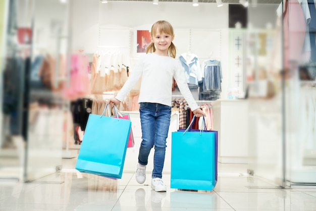 Child keeping bags and posing while going out from store