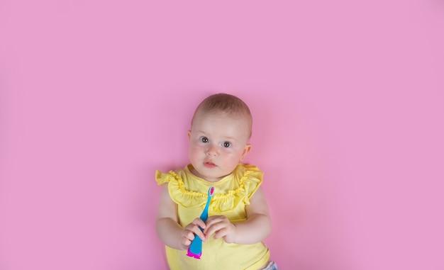 Зубы девушки ребенк ребенка чистя щеткой на розовой предпосылке. здравоохранение, гигиена полости рта, люди и концепция красоты. мокап, свободное место.