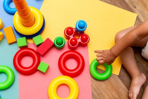 明るい背景にカラフルな教育おもちゃパターンの背景を遊んでいる子供の子供