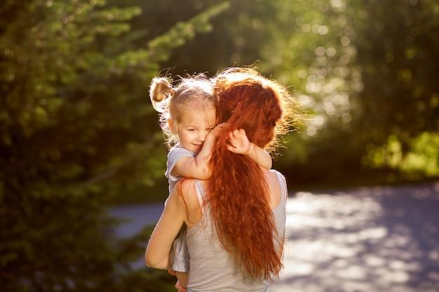 아이는 공원에서 그녀의 엄마를 키스하고 포옹