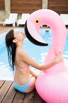 Child kissing flamingo floater head