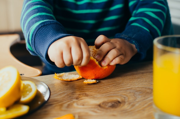 The child in the kitchen, cleans the mandarin,standing next to the juice and sliced lemon in a bowl