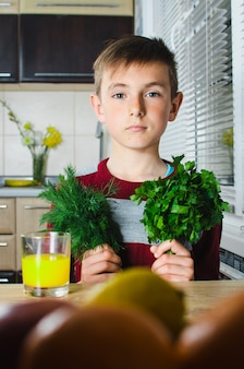 The child in the kitchen with herbs dill and parsley, smiles and shows her