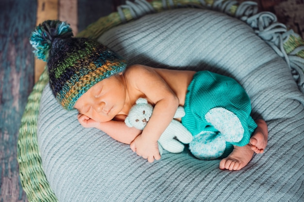 Child in knitted hat sleeps on large blue pillow