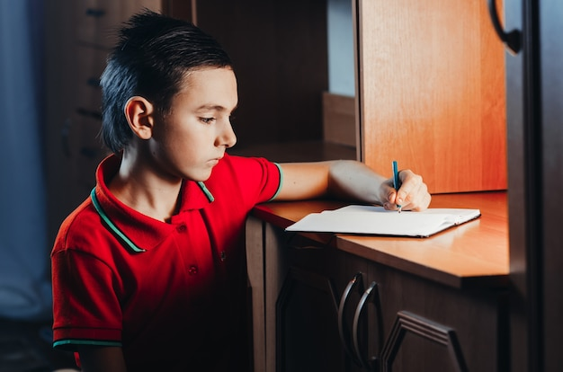 The child late at night writing in a notebook, doing homework,set goals