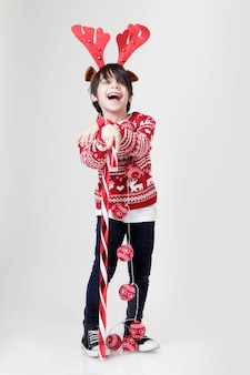 Child laughing with christmas clothes and decorations