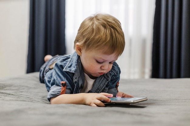 Child laying on the bed and using mobile phone