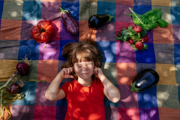 Child laying on checkered blanket outdoors with vegetables