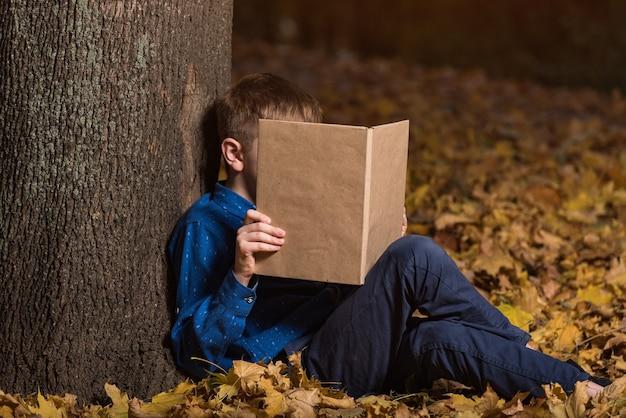 Ребенок оперся на ствол дерева и глядя на книгу. мальчик в осеннем лесу с книгой. копировать пространство. макет.