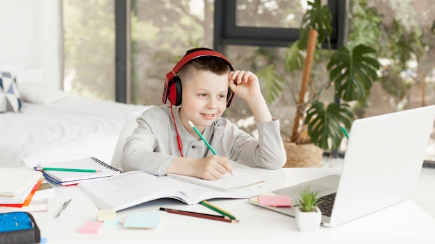 Child learning courses online and wearing headphones