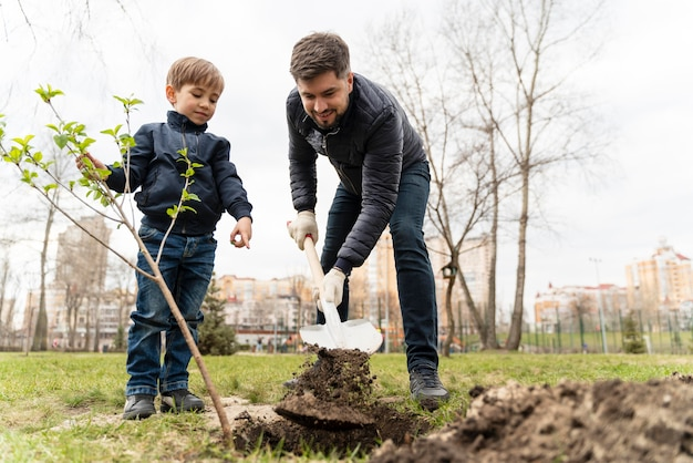 Child learning how to plant a tree