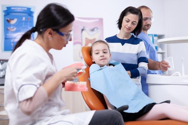 Ребенок учится пользоваться зубной коркой от молодого дантиста в. маленькая девочка и мать слушают стоматолога, говорящего о гигиене зубов в стоматологической клинике, держащей модель челюсти.