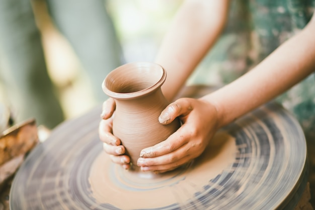 Child learning to sculpt a clay pot