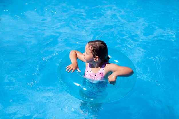 A child learning to swim is held for safety by a blue transparent inflatable circle in the sea the c...