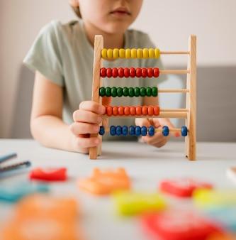 自宅でそろばんの使い方を学ぶ子供